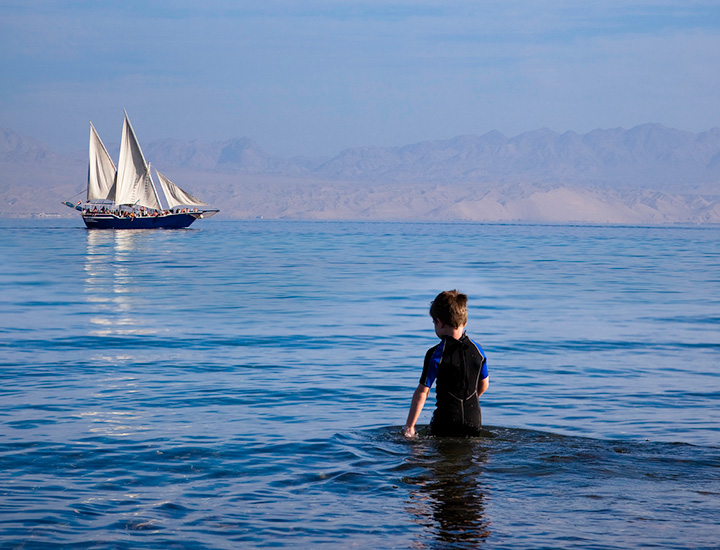 a sailing boat in the red sea and a little boy wading in the water